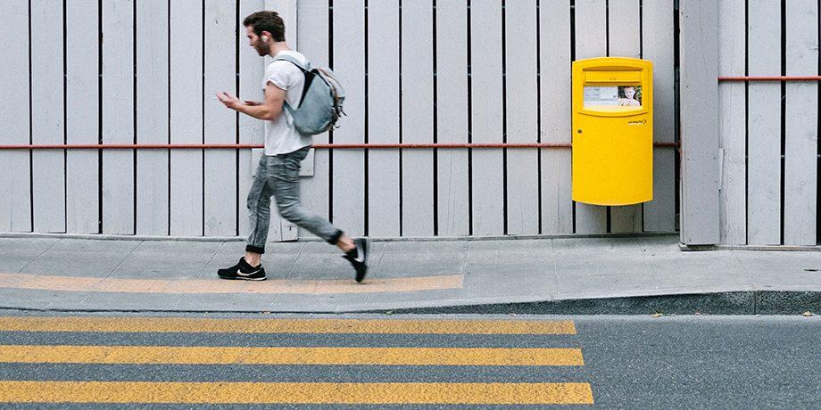 Young man walking near a zebra crossing