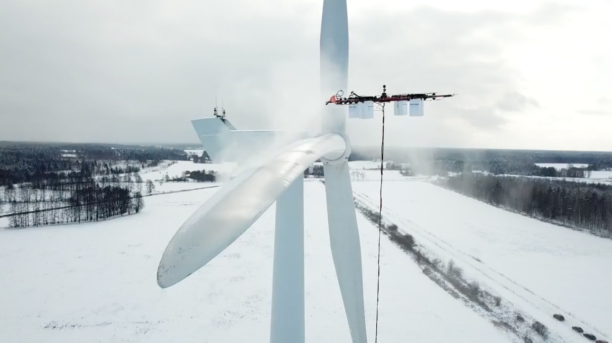 Drone removing snow from a wind turbine