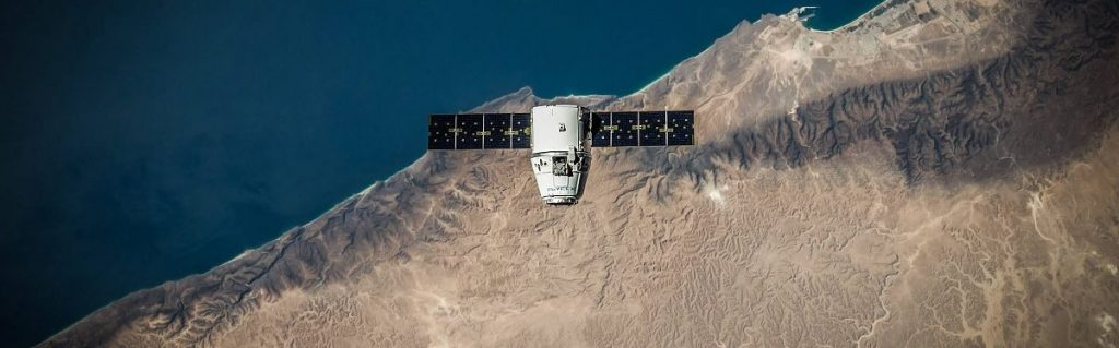 Imagen desde arriba en la que se ve un satélite sobrevolando parte de tierra y parte de mar