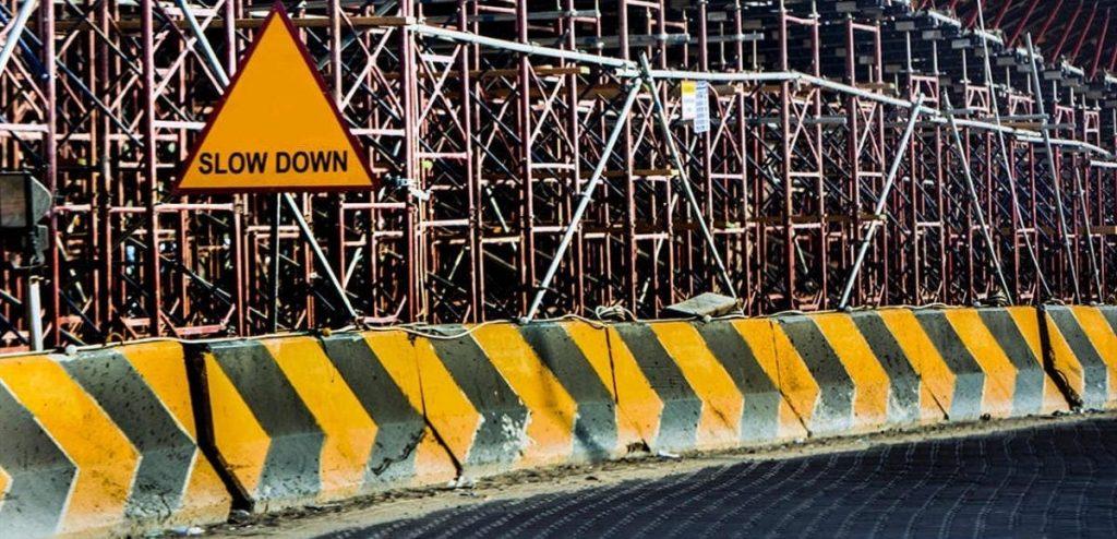 Foto de barreras pintadas en amarillo y negro para avisar de una obra, colocado delante de andamios y una señal