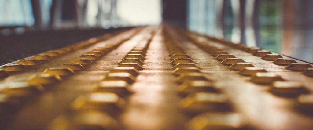 Foto de un tramo de pavimento podotactil que marca el fin de un anden