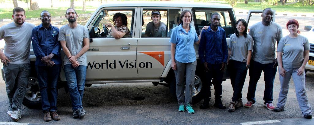 Image of a group of donors from different organizations posing in front of a jeep