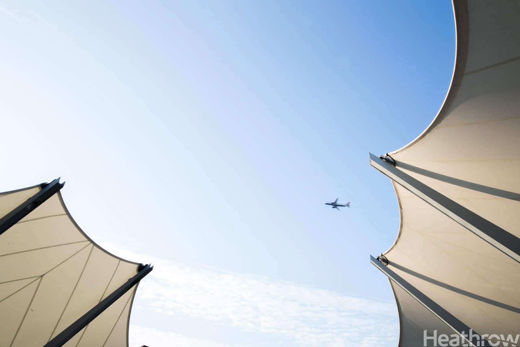 An airplane flies over the drop off area at T5