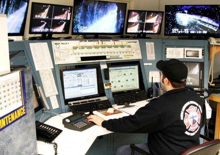 Foto de un controlador de espaldas rodeado de monitores