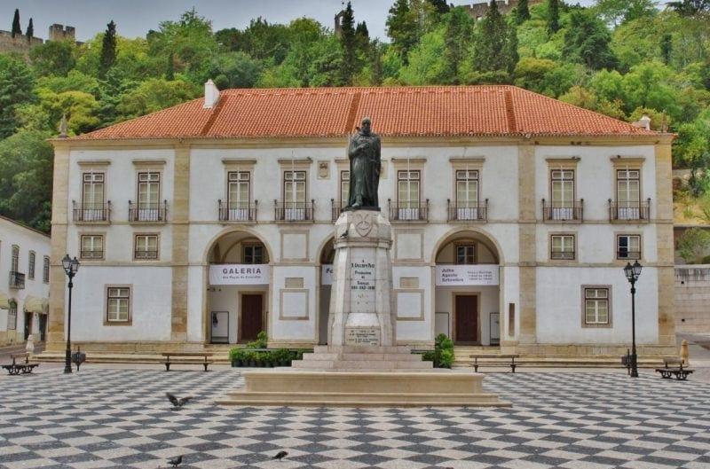 Foto de una plaza con un palacete y una estatua en medio