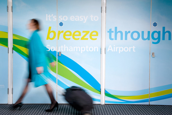 Southampton Airport, Departures Hall, passenger with luggage passes airport sign,