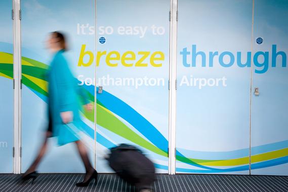 Foto de una puerta de entrada al aeropuerto de Southampton y una mujer pasando por delante con una maleta