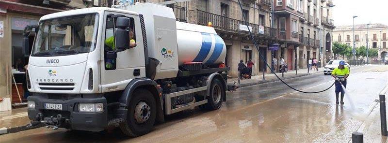 Foto de un operario de limpieza y un camion limpiando una calle de Tafalla tras las inundaciones