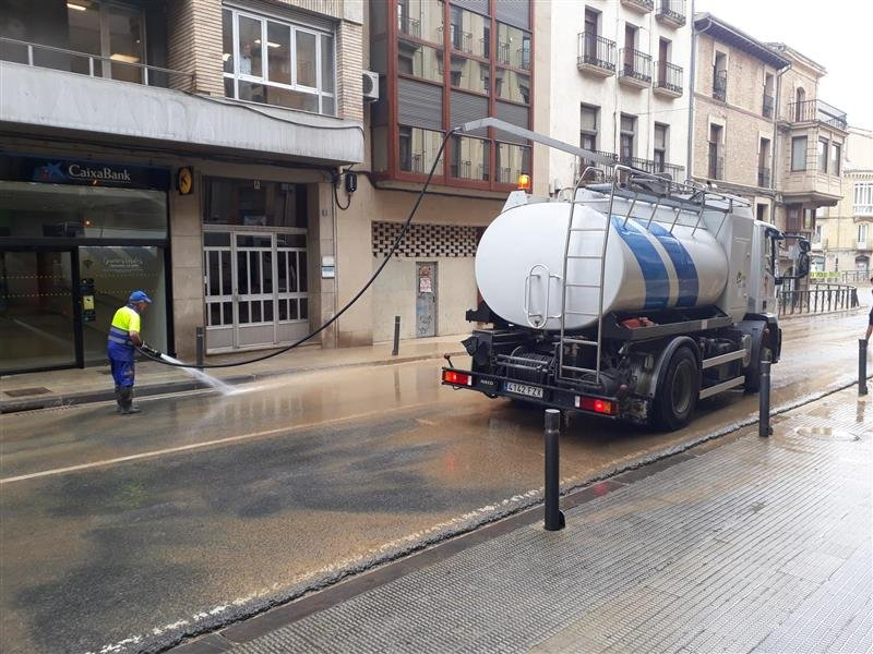 Photo of a cleaning worker and a truck cleaning a street in Tafalla