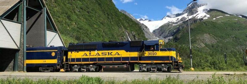 Foto de un tren saliendo de la estación en un paisaje montañoso