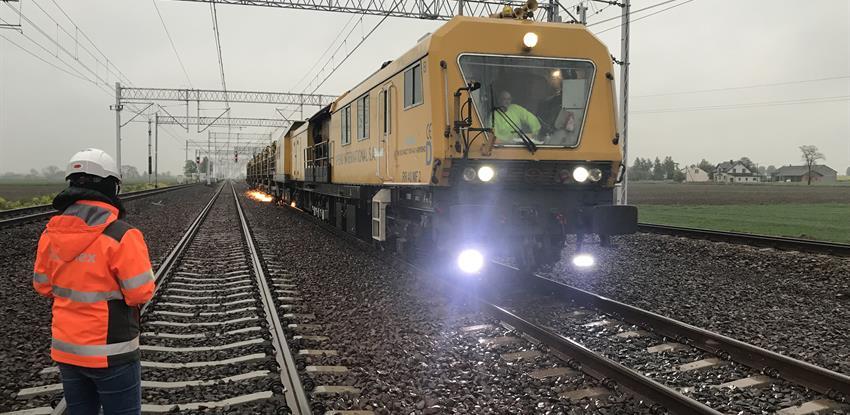 Foto de un tren, vías, catenaria y 2 operarios