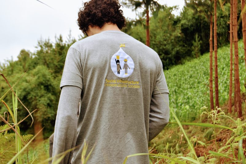 Imagen de un chico de espaldas con una camiseta de Infraestructuras Sociales de Ferrovial